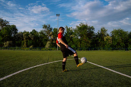 Young male soccer player juggles a ball on a soccer field.Athlete juggling the football with his feet in stadium.Football sports concept