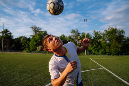 Young male soccer player juggles a ball on a soccer field.sport, football and people - soccer player playing and juggling ball using header technique on field.Football sports concept Stock Photo