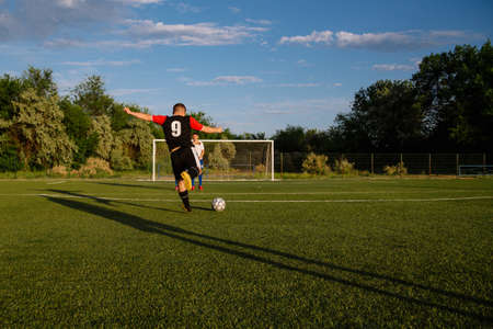 Soccer player kicks the ball.Soccer player takes the free-kick.Football player kicks the ball on the football field.Football sports concept