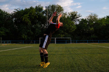 soccer player celebrating goal on a soccer stadium.Soccer player does a backflip.Happy soccer player celebrate a victory on a football stadium Stock Photo