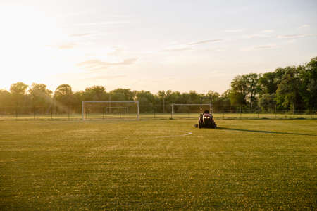Cleaning football lawn. A man mowing the grass at the football stadium. Man on a tractor.Worker on a tractor works on a football field