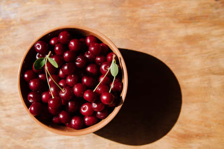 Fresh cherry on plate on wooden background. fresh ripe cherries. sweet cherries.Sweet red cherries in a plate on a wooden background