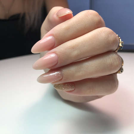 Hands of a woman with pink manicure on nails.Manicure beauty salon concept. Empty place for text or logo.