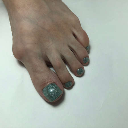 Green pedicure. Green pedicure on female feet.Woman feet with green pedicure on gray background Фото со стока