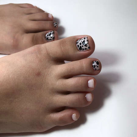Pink pedicure. Pink pedicure on female feet.Woman feet with Pink pedicure on gray background