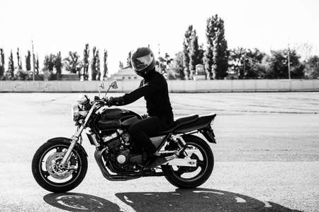 Man rides a motorcycle in the city.Young man in helmet and equipment rides a motorcycle on the road.Motorcyclist riding a bike during the day on the road.Black and white photo Stockfoto
