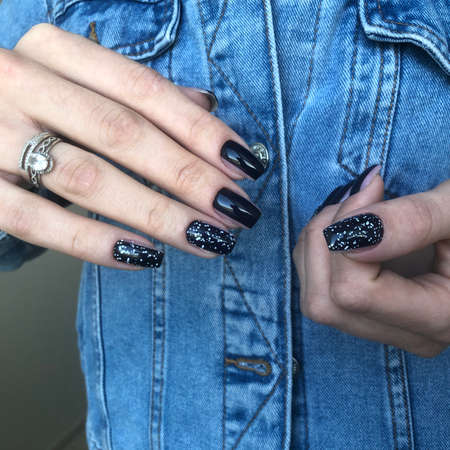 Hands of a woman with black manicure on nails.