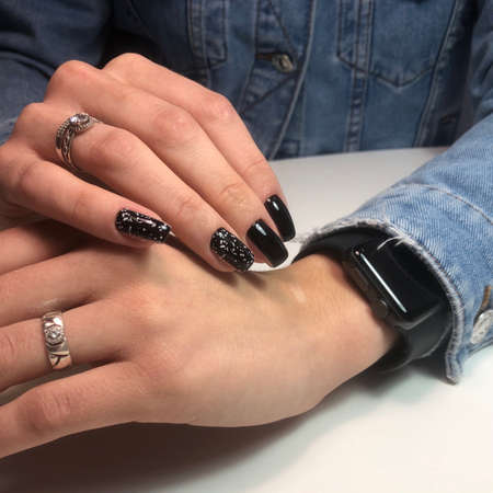 Hands of a woman with black manicure on nails