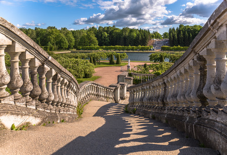 petergof: Shadows of old stairs to green garden under blue sky with bulky clouds in summer Petergof