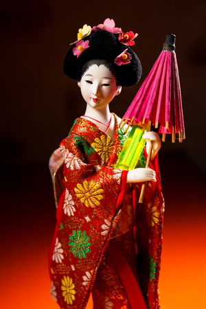 isotope: Japanese female kimono doll wearing red paper umbrella with flowers in hair and green glowing tritium trinket