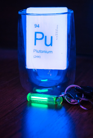 luminescent: Green glowing tritium trinket on wooden desktop with luminescent soap