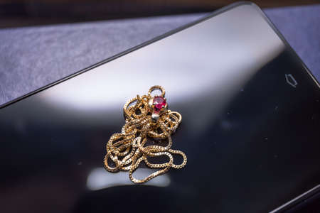ruby stone: A closeup view of a ruby ??stone with gold necklace on black cell phone surface