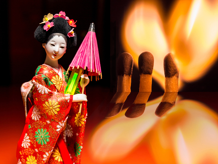 A concept of chemical and nuclear fire: a flaming heart from matchsticks and a kimono Japanese girl keeping glowing trinket with luminescent radioactive tritium Stock Photo