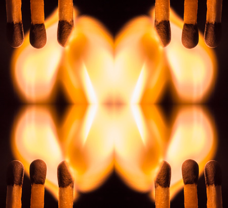 Kaleidoscopic view of ignited matches on dark background