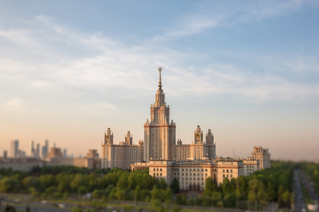 soften: Soften edge view of sunset Moscow university framed with green trees under cloudy sky