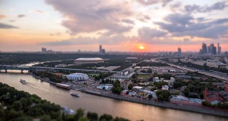 Tilt and shift view of sunset panorama of Moscow with pink clouds, traveling boats and red river reflections under the bridge on horizon line