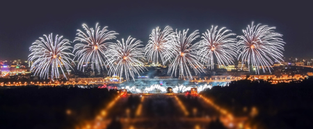 Soften edge view of Moscow firework festival in the Lenin Hills area with thousands of smart phone flashes and water reflections Stock Photo