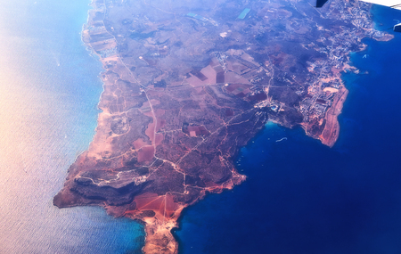Aerial view of the Cyprus island surrounded by azure sea with waves, yacht, city relief and coastline