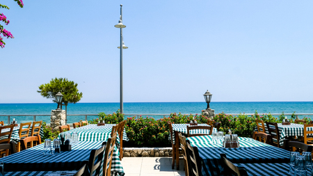 Typical interior of Cyprus restaurant with flowers and blue sea