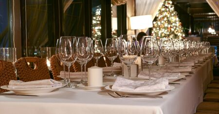 New year service in restaurant with transparent glasses, illuminated evergreen tree, multiple reflections and defocused background