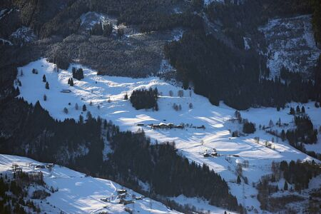 Aerial view of winter Austria valley village from high point of sunny Alp mountains