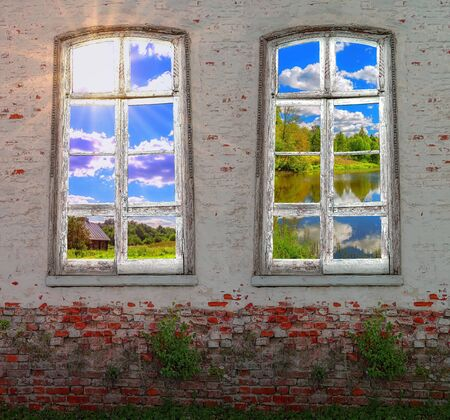 Conceptual view on countryside landscape from retro window in the middle of abandoned brick wall with growing green plants