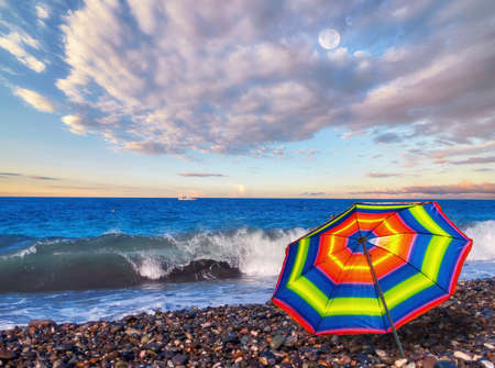 Panoramic view of rainbow umbrella on summer beach of tropical sea with azure waves and white ship under dramatic cloudy sky Standard-Bild