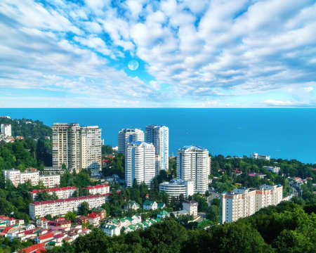 Aerial view of blue coast of Black Sea near Sochi city with residential houses and recreation area under dramatic cloudy sky in sunny summer