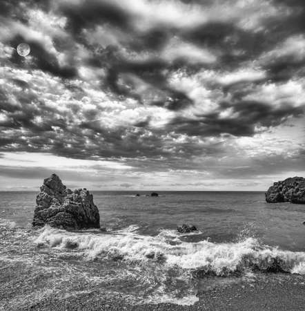 Landscape monochrome view over the famous blue bay near the birthplace of Aphrodite in Cyprus in summer under dramatic cloudy sky