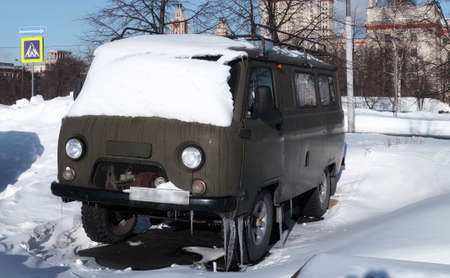 Old Russian all-terrain famous retro vehicle under snow and blue sunny sky in the campus of old university in Moscow