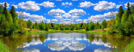 Seamless vibrant kaleidoscopic pattern of river reflections, green summer forest and blue cloudy sky Reklamní fotografie