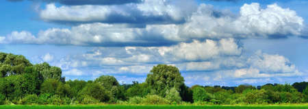 Sunny countryside landscape under summer dramatic clouds