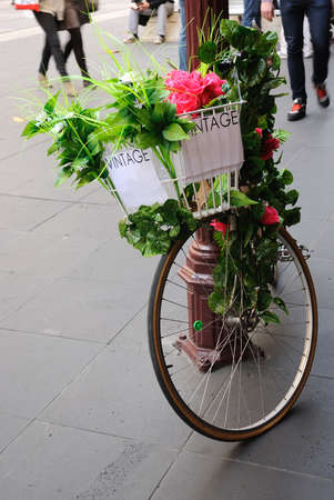 Vintage bicycle with flowers in the front basket parked in the city