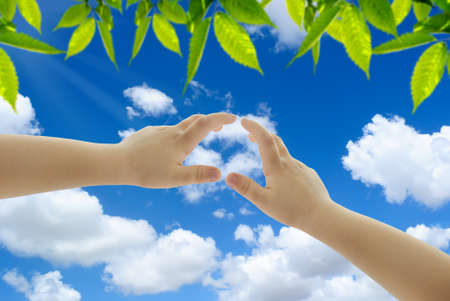 Hands of a child reaching out to the cloud shaped as a heart Stock Photo - 14230744