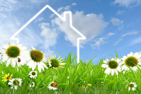 Symbol of a house on grassland against blue sky photo