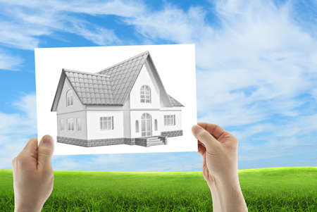 Human hands holding three dimensional house sketch a of a future house photo