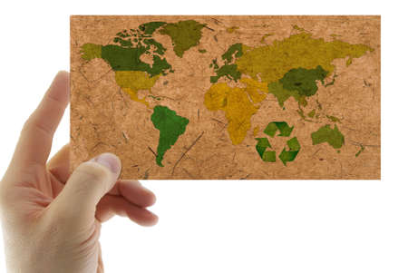 Recycled paper with map of the world in the hand, isolated on a white background. photo