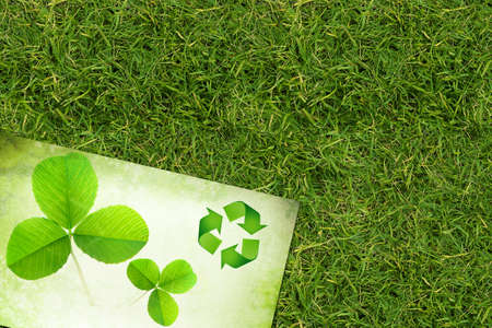 Ecology background with recycling symbol and clover over green grass photo