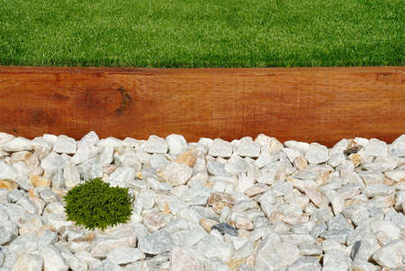 Landscaping combinations of grass timber and stones Stock Photo