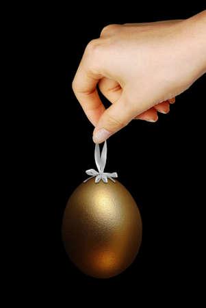 Golden Easter egg isolated on black background photo