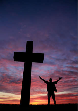 mystery of faith: Dramatic sky scenery with a cross and silhouette of a praying man