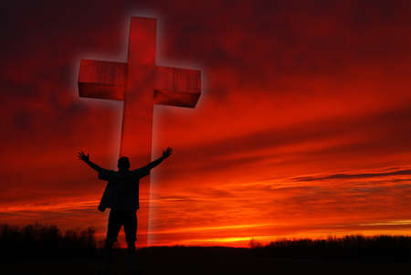 Dramatic sky scenery with a cross and silhouette of a praying man photo