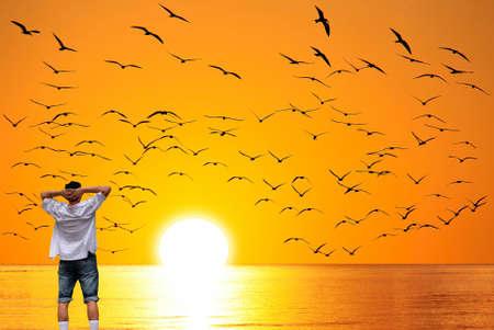 Single male standing on beach facing beautiful ocean
