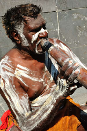 Australian Aboriginal busker playing didgeridoo in central city Editorial
