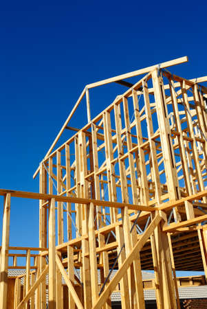 New residential construction house framing against a blue sky