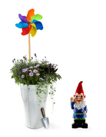 Spring flowers in an aluminum bucket with a toy windmill and gnome