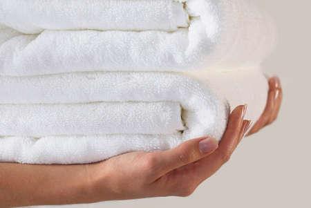 Mãos fêmeas que prendem uma pilha de toalhas brancas Imagens