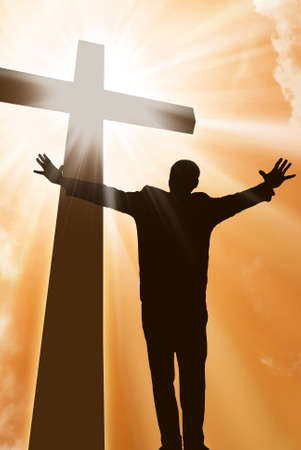 goodness: A man praising a cross of Jesus with light beams Stock Photo