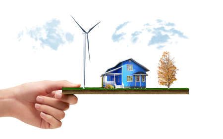 Hand holding green meadow with countryside house and wind mill turbine, concept for ecology or alternative energy