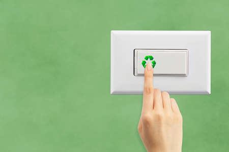 Light switch and hand on a green wall background, ecology concept photo